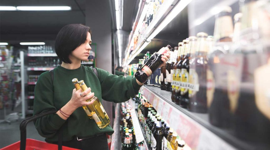 young woman buying alcohol in a super market