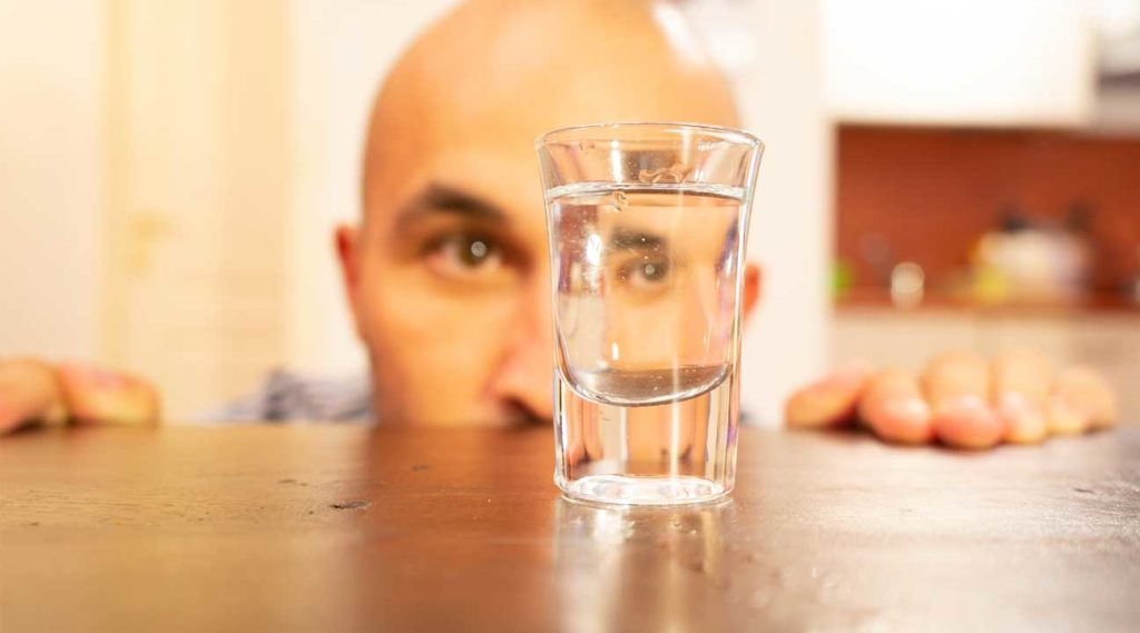 man looking at an empty shot glass