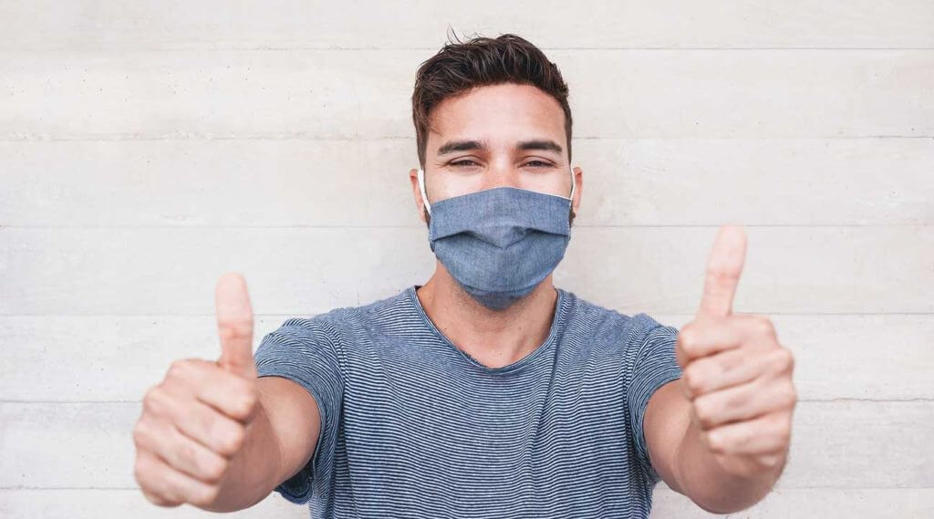 young man wearing a mask smiling and giving two thumbs up