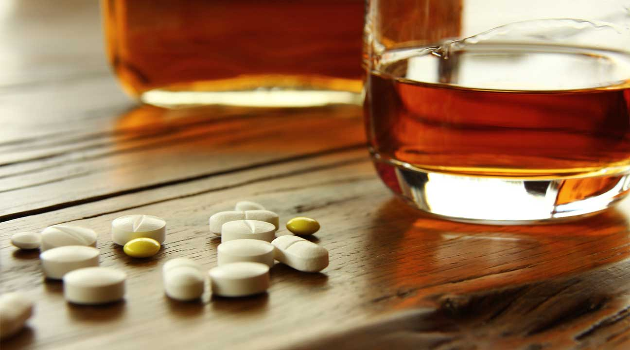 various colorful pills and alcohol whiskey on a table