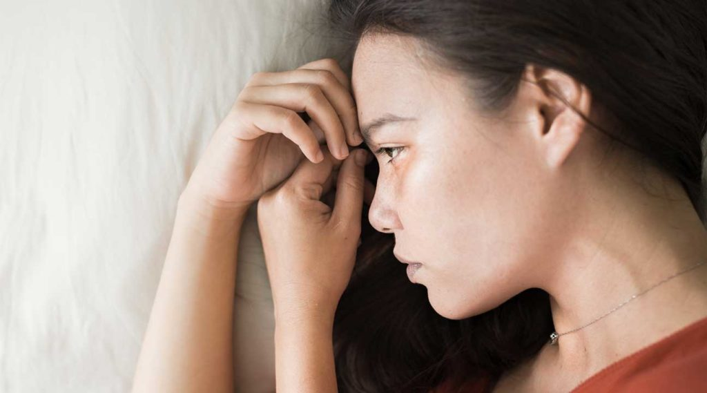 young woman laying down experiencing Fentanyl Withdrawal Symptoms