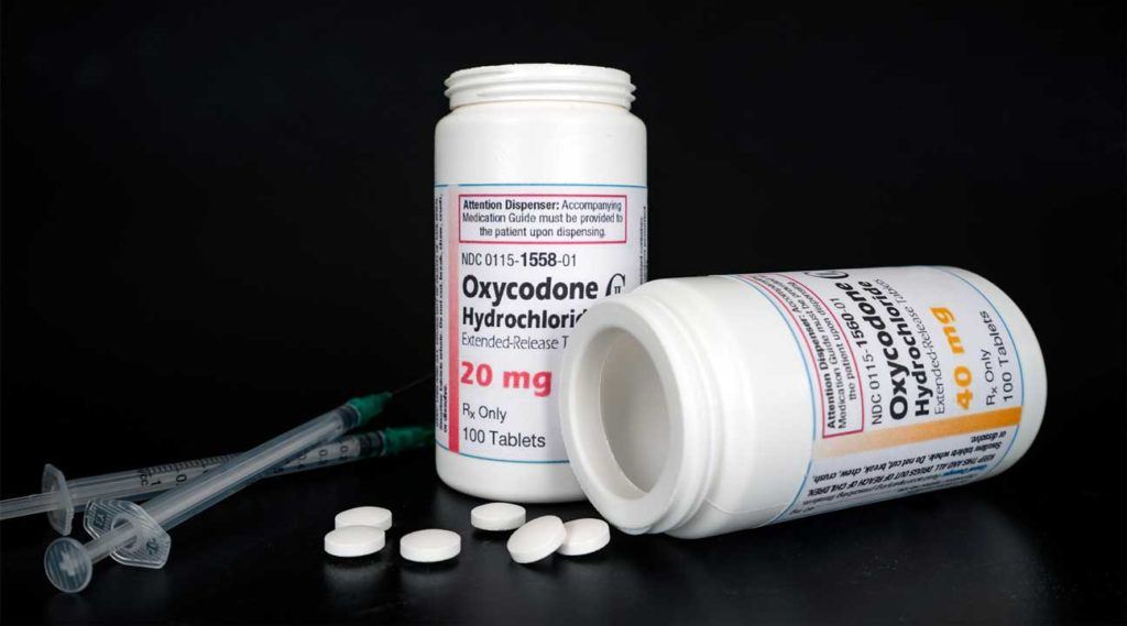 syringes next to two bottle of Oxycodone Hydrochloride