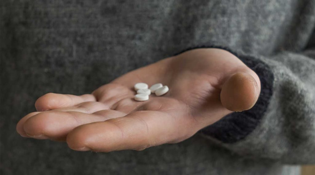 young man attempting to take a handful of Oxycodone opioid pills