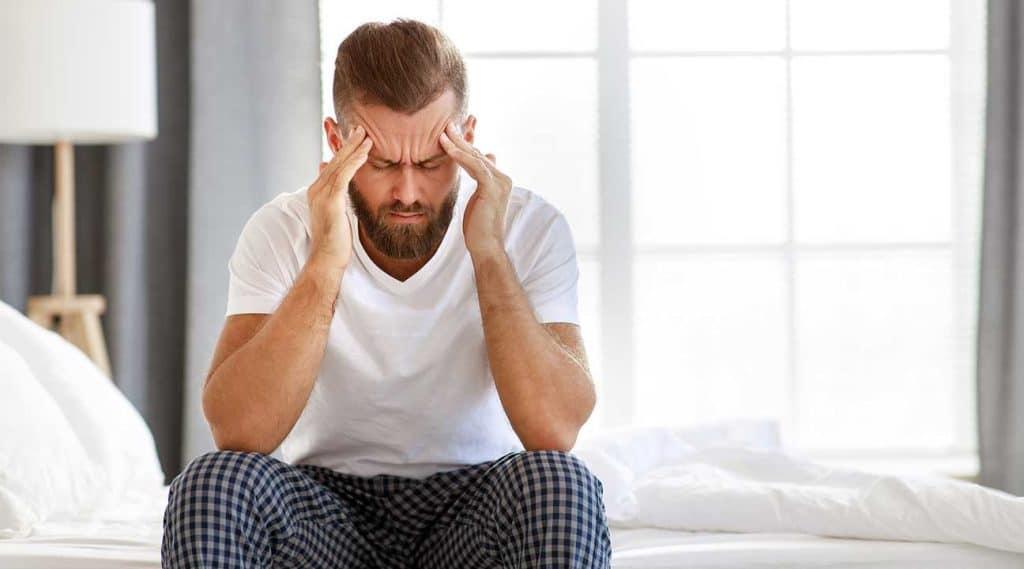 man holding his head experiencing Halcion Withdrawal symptoms