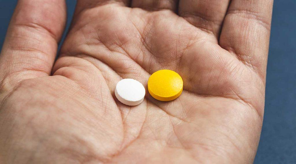 Methadone Vs. Suboxone man holding a white pill and orange pill