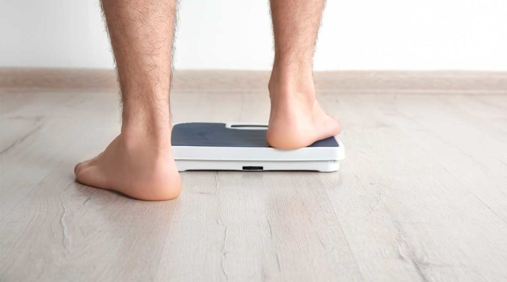 Methadone Maintenance Cause Weight Gain Man stepping onto a scale to check his weight